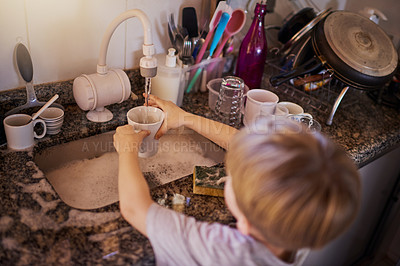 Buy stock photo High angle shot of a little boy washing dishes in the kitchen at home