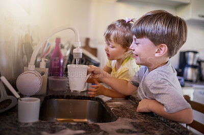 Buy stock photo Shot of two adorable little siblings washing dishes together in the kitchen at home