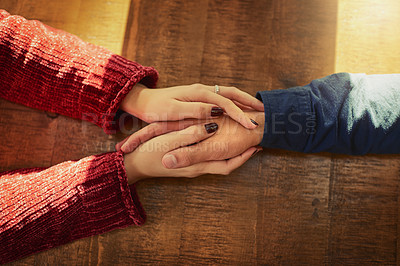 Buy stock photo Cropped high angle shot of an unidentifiable man and woman holding hands on a table