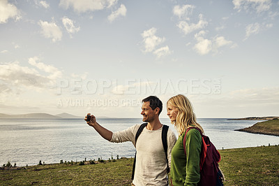 Buy stock photo Cropped shot of an attractive young couple taking a selfie while spending the day in nature