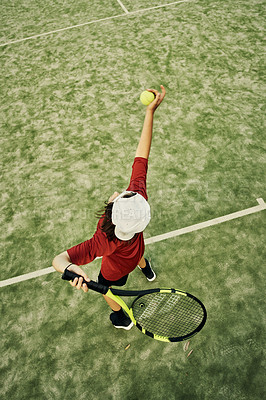 Buy stock photo High angle shot of a young boy working on his serve during tennis practice