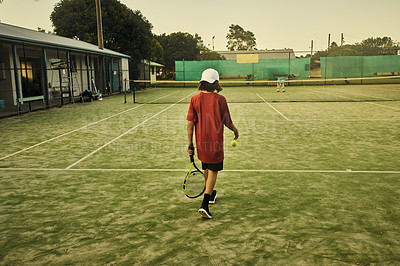 Buy stock photo Rearview shot of a young boy playing tennis