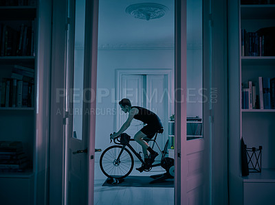 Buy stock photo Shot of a young man working out on an exercise bike at home