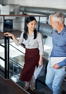 Buy stock photo Shot of two businesspeople having a discussion while walking up a staircase in an office