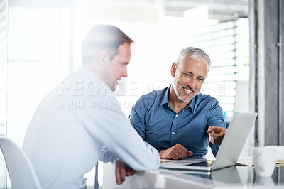 Buy stock photo Shot of two businessmen using a laptop together in a modern office