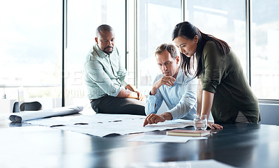 Buy stock photo Shot of a group of businesspeople drafting a blueprint together in a modern office