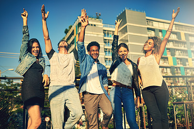 Buy stock photo Cropped shot of a group of young diverse friends spending the day outside on a rooftop