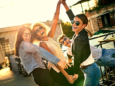 Buy stock photo Cropped shot of a group of young friends spending the day outside on a rooftop
