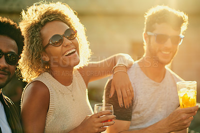 Buy stock photo Cropped shot of a group of young diverse friends having a drink and spending the day outside on a rooftop
