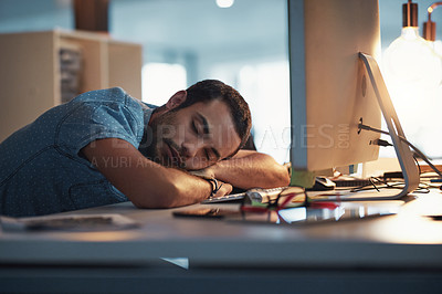 Buy stock photo Cropped shot of a young businessman taking a nap on his desk in a modern office at night