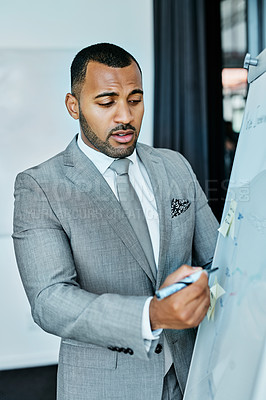 Buy stock photo Shot of a young businessman writing on a whiteboard in an office