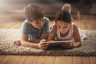 Buy stock photo Shot of an adorable brother and sister using a digital tablet together on the floor at home