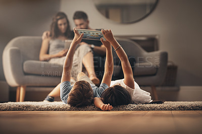 Buy stock photo Shot of an adorable brother and sister using a digital tablet at home with their parents in the background