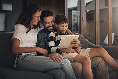 Buy stock photo Shot of an adorable little boy using a digital tablet with his mother and father on the sofa at home