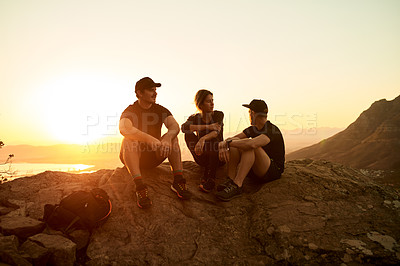 Buy stock photo Full length shot of three young friends sitting down while taking a break from their mountain hike