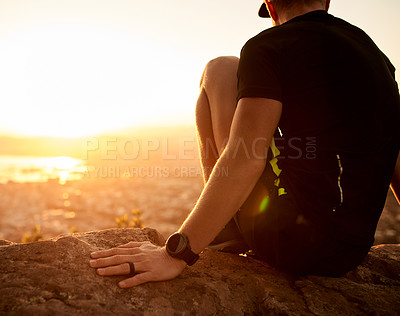 Buy stock photo Rearview shot of an unrecognizable young man taking in the views during his hike in the mountains