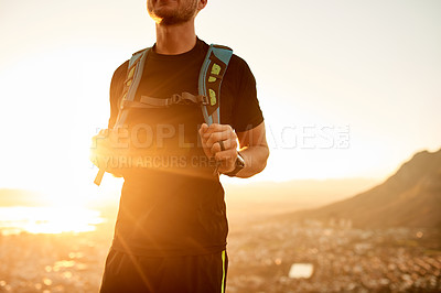 Buy stock photo Cropped shot of an unrecognizable young man enjoying an early morning hike in the mountains