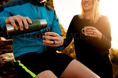 Buy stock photo Cropped shot of an unrecognizable young couple taking a coffee break during their mountain hike