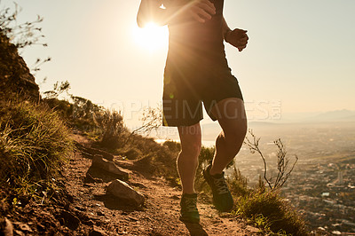 Buy stock photo Cropped shot of an unrecognizable young man taking an early morning hike through the mountains