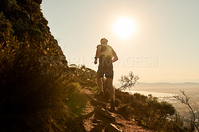 Buy stock photo Rearview shot of an unrecognizable young man taking an early morning hike through the mountains