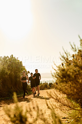 Buy stock photo Full length shot of a group of friends taking an early morning hike through the mountains