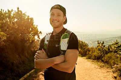 Buy stock photo Cropped portrait of a handsome young man standing with his arms folded during a hike in the mountains