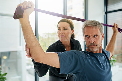 Buy stock photo Shot of a focussed middle aged man doing a stretch exercise with an elastic rope while being helped by a trainer inside of a gym