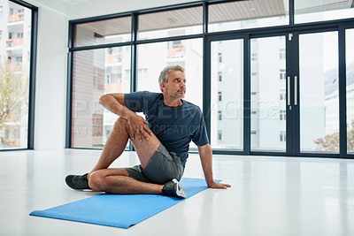 Buy stock photo Shot of a focused middle aged man doing stretch exercises on a mat inside of a studio during the day