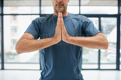 Buy stock photo Shot of an unrecognizable middle aged man doing yoga poses and holding his hands together while standing inside of a studio during the day