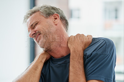 Buy stock photo Shot of a uncomfortable looking middle aged man holding his shoulders due to pain while being seated on the floor of a fitness studio