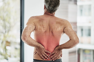 Buy stock photo Rearview shot of an unrecognizable middle aged man holding his back due to pain while standing without a shirt inside of a fitness studio
