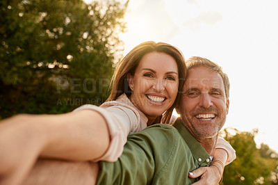 Buy stock photo Cropped shot of a handsome mature man piggybacking his beautiful wife outside