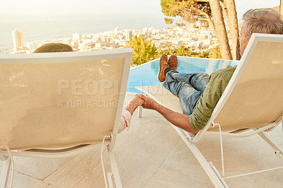 Buy stock photo Rearview shot of an affectionate mature couple sitting on deckchairs outdoors