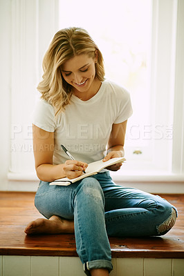 Buy stock photo Shot of an attractive young woman writing in a book at home