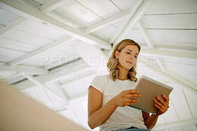 Buy stock photo Shot of an attractive young woman using a digital tablet during a relaxing day at home