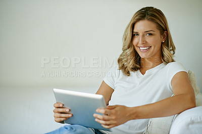 Buy stock photo Portrait of an attractive young woman using a digital tablet while relaxing on the sofa at home