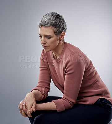Buy stock photo Studio shot of a mature woman looking sad against a gray background