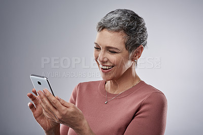 Buy stock photo Studio shot of a mature woman using a mobile phone against a gray background