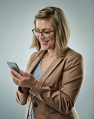 Buy stock photo Studio shot of an attractive young businesswoman using a mobile phone against a gray background
