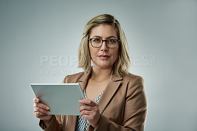 Buy stock photo Studio portrait of an attractive young businesswoman using a digital tablet against a gray background