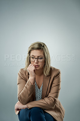 Buy stock photo Studio shot of an attractive young businesswoman looking worried against a gray background