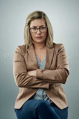 Buy stock photo Studio portrait of a young businesswoman looking stern against a gray background