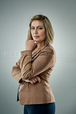 Buy stock photo Studio portrait of a confident young businesswoman against a gray background