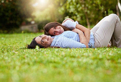 Buy stock photo Portrait of a cheerful mother and her young daughter lying on grass inside a park outside during the day