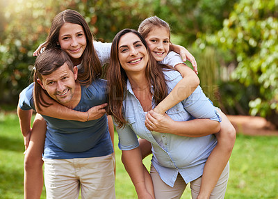 Buy stock photo Portrait of a cheerful young mother and father giving their daughters a piggyback ride outside in a park during the day