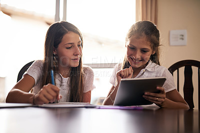 Buy stock photo Shot of two cheerful young girls doing homework together around a table while making use of a digital tablet inside at home during the day