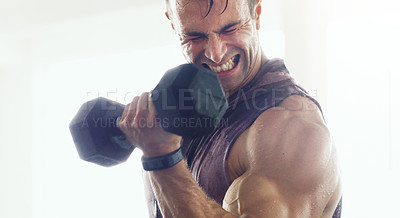 Buy stock photo Shot of a muscular young man lifting weights in a gym