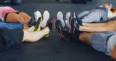Buy stock photo Cropped shot of a group of people lying together in a circle during their workout at a gym