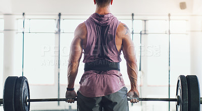Buy stock photo Rearview shot of a muscular man lifting a barbell in a gym