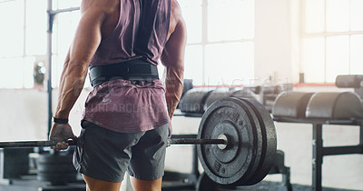 Buy stock photo Cropped shot of a muscular man lifting a barbell in a gym